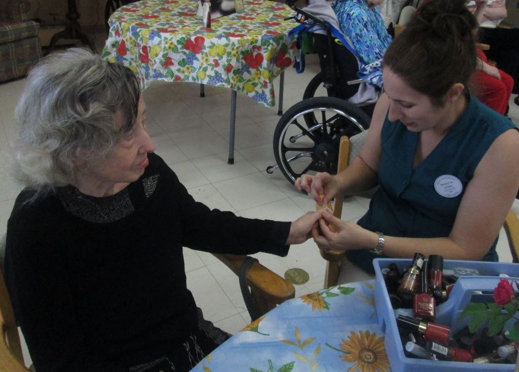 Resident Charlotte Stolovitch is getting her nails done by staff member Patricia Lewis