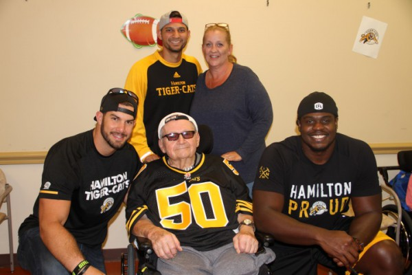 Three Hamilton Tiger Cats players pose alongside a male resident and a female staff member