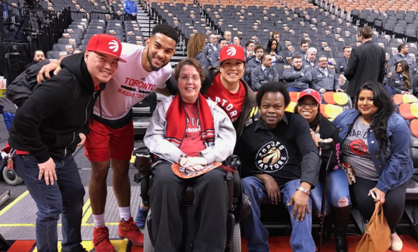 Cathy, Garfield and accompanying staff sit courtside. Raptor Corey Joseph poses for a picture with the group.