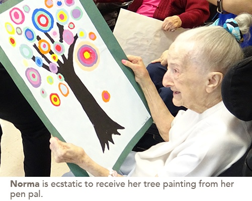 Resident Norma smiles looking at a child's painting of a tree