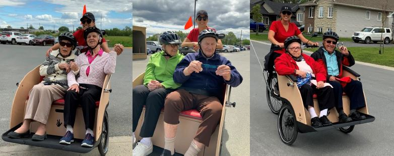 six different residents in pairs of 2 enjoying cycling, posing with a staff member behind them