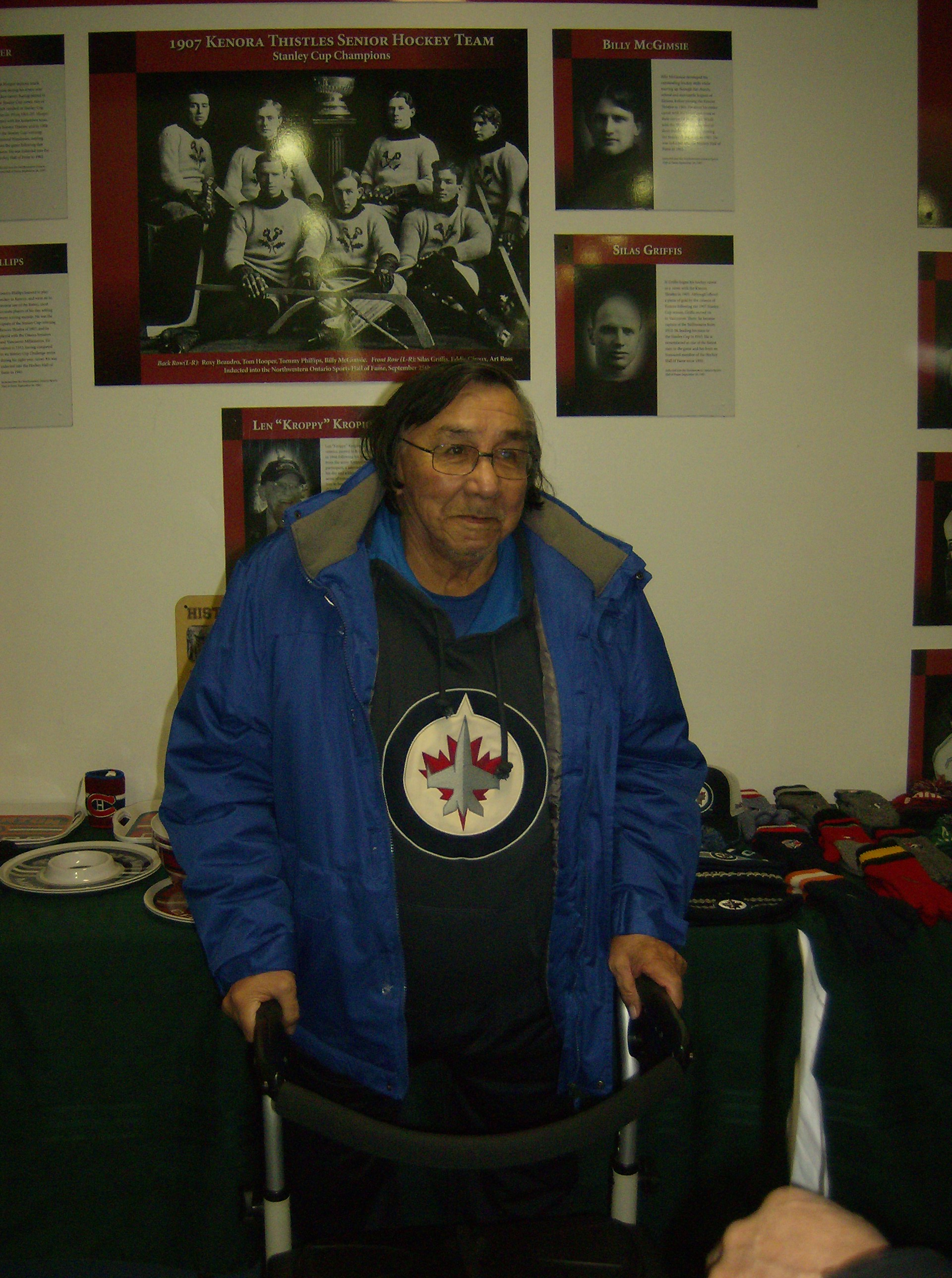 Joe Hunter stands with his walker in front of First Nations hockey posters