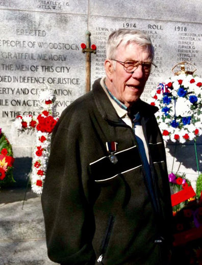 Leonard Scott, a veteran of the British Royal Air force, in front of the Woodstock Cenotaph. He is wearing his medial for Distinguished Service and Devotion to Duty