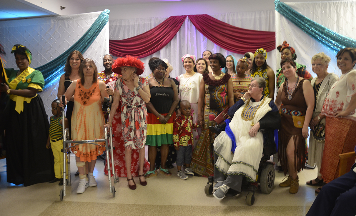Residents, family members and staff who were in the fashion show pose together in their outfits