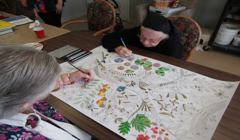Residents Mary G. and Anna W. working on a collective art project, entitled Tree of Life