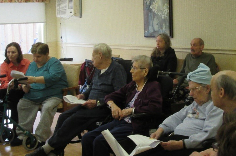 Residents read aloud from handouts during a club meeting