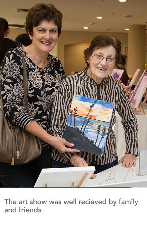 A resident and her daughter pose, holding up a painting made by a resident