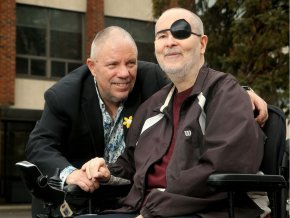 Paul sits in a wheelchair with a patch over one eye, joined by another man, his husband